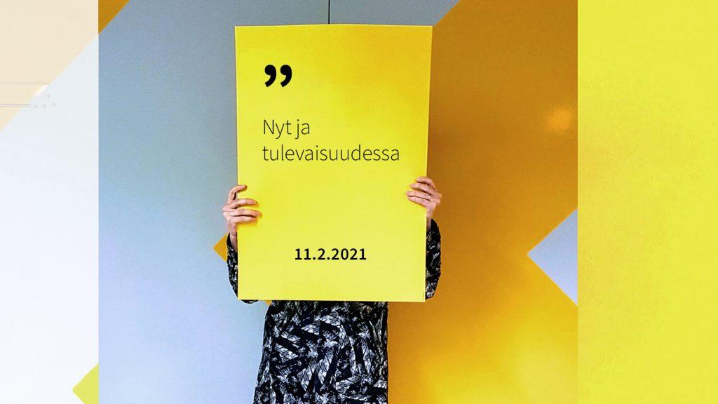 Henkilö pitää käsissään kylttiä, jossa lukee Nyt ja tulevaisuudessa 11.2.2021.