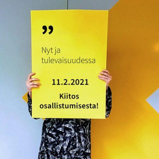 Henkilö pitää käsissään kylttiä, jossa lukee Nyt ja tulevaisuudessa 11.2.2021 kiitos osallistumisesta.